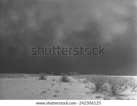 Heavy black clouds of dust rising over the Texas Panhandle, Texas. March 1936 photo by Arthur Rothstein. - stock photo