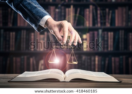 Heavy books and gold of the balance - stock photo