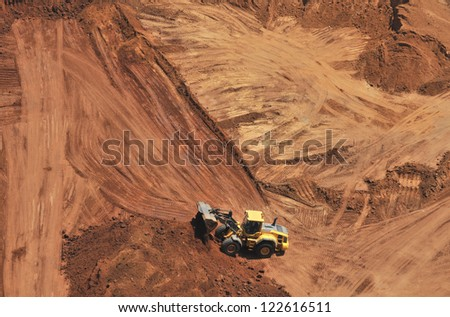 Heavy bulldozer loading red sand, an aerial view - stock photo