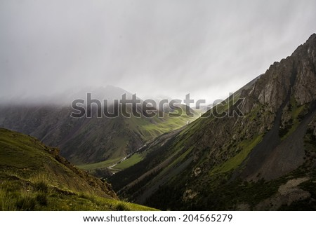 Heavy clouds above high mountains. Rainy weather - stock photo