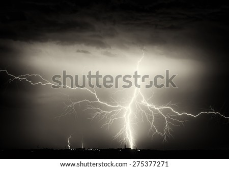 Heavy clouds bringing thunder, lightnings and storm over city on horizon. - stock photo