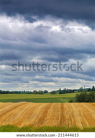 Heavy clouds over the field  - stock photo