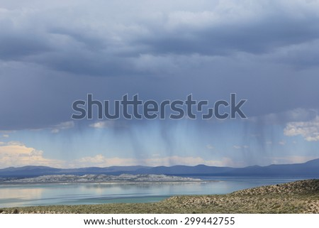 """Heavy clouds produce visible bands of rain, called """"virga,"""" above Mono Lake in California. - stock photo"""