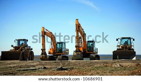 Heavy construction equipment backhoe bulldozer - stock photo