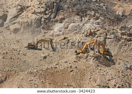 Heavy construction equipment clinging to the face of a steep hill - stock photo