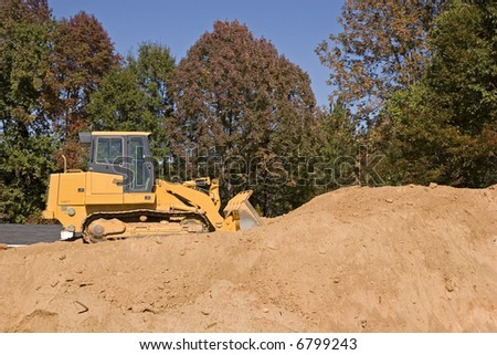 Heavy construction equipment on top of a large pile of dirt - stock photo
