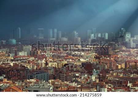 Heavy dark clouds over the skyline of Barcelona partly light of sunbeam - stock photo