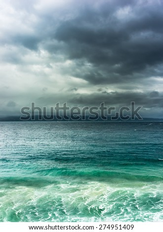 Heavy dramatic clouds over stormy sea with land on horizont - stock photo