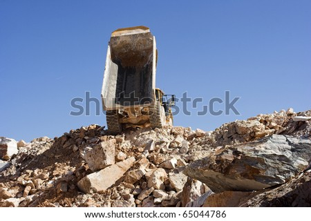 Heavy dump truck against blue sky operating in a marble quarry - stock photo