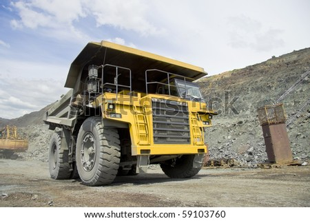 Heavy dump truck driving through the opencast - stock photo