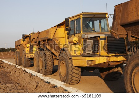 Heavy dump trucks lined up at a construction site. - stock photo
