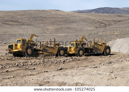 Heavy duty earth scrapers operating in tandem - stock photo