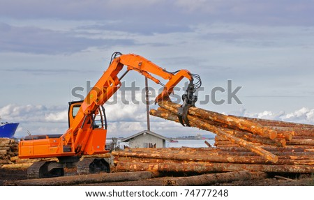 Heavy duty orange claw like logging machine for picking up and piling logs with river and ship in background - stock photo