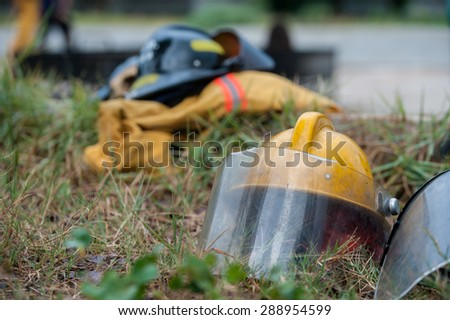 Heavy Duty Protective Fire Fighting Cloth, Gloves, Helmet, Jacket, Pants, on Green Grass Background - stock photo