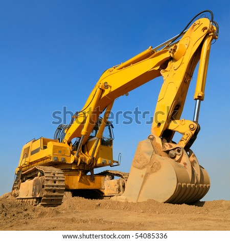 Heavy earth mover on a sunny day with the blue sky in the background - stock photo