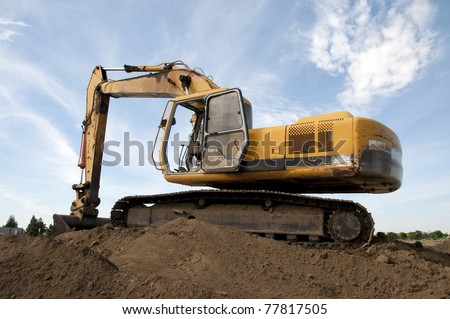 Heavy equipment prepares construction job site: Articulated boom and digging bucket - stock photo