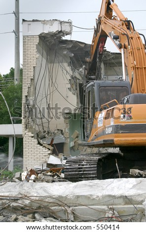 Heavy equipment tearing down a brick building