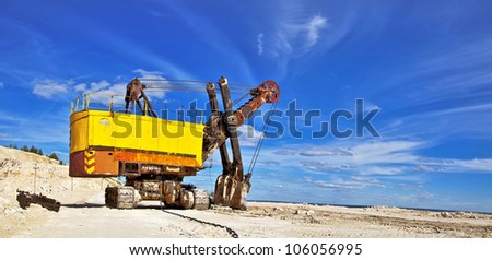 Heavy excavator in quarry for the extraction of gravel. Against the background of blue sky.