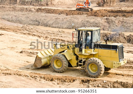 Heavy excavator loader at soil moving works at construction site - stock photo