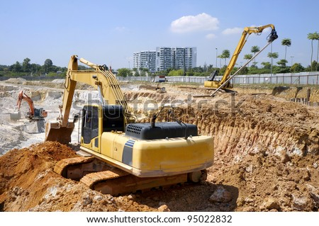 Heavy excavator loader at soil moving works in construction site. - stock photo