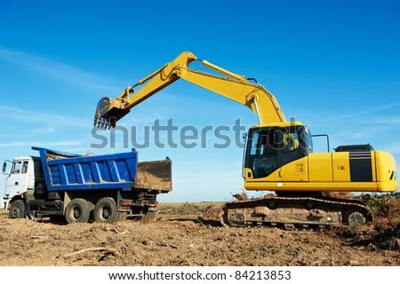 Heavy excavator loader at soil moving works in summer sandpit - stock photo