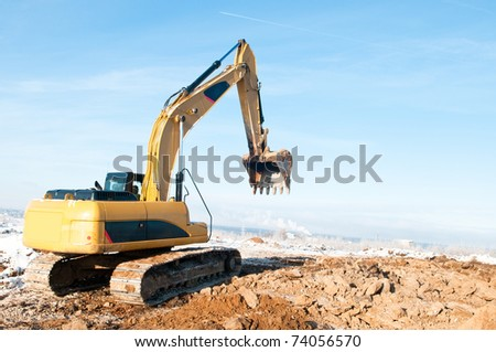 Heavy excavator loader at winter frozen soil moving works in sandpit - stock photo