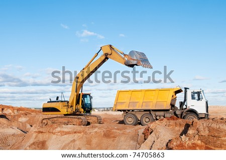 Heavy excavator loading dumper truck with sand in quarry over blue sky