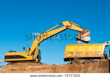 Heavy excavator loading dumper truck with sand in quarry over blue sky - stock photo