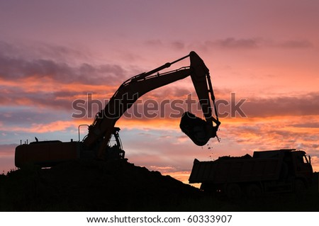Heavy excavator loading dumper truck with sand in sandpit at dawn - stock photo