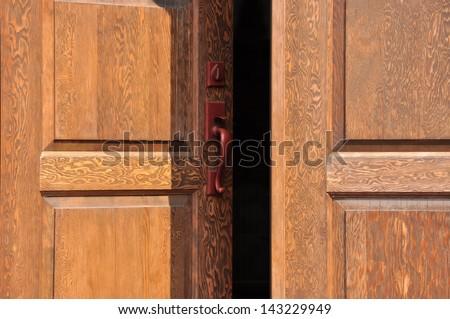 Heavy firs doors in the sunlight, slightly open. - stock photo