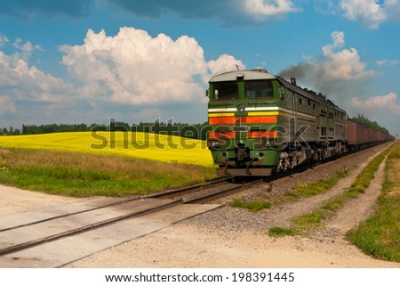 Heavy freight train fill with coal and country road landscape. - stock photo