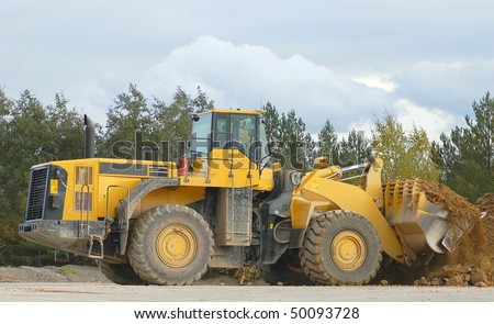 Heavy front loader in action - stock photo