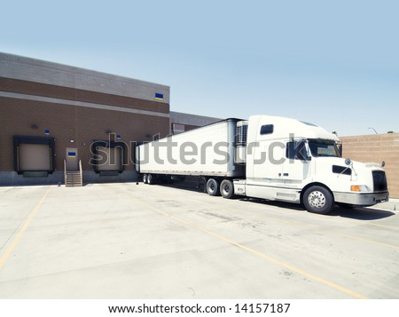 Heavy goods truck at loading bay - stock photo