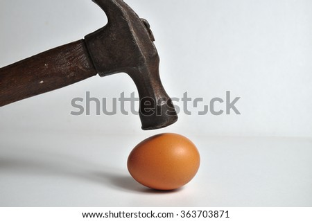 Heavy hammer on the way to crash an egg. Conceptual themes - stock photo