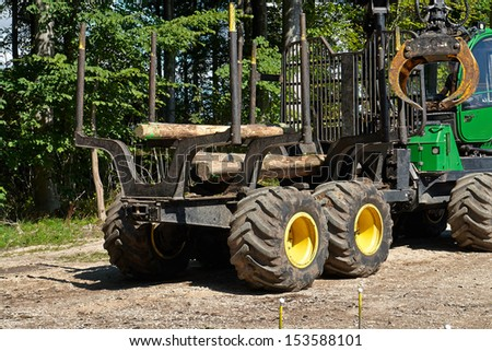 Heavy harvester loader truck doing forestry work in the forest with logs - stock photo