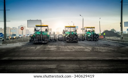 Heavy industrial machines laying asphalt on new road - stock photo