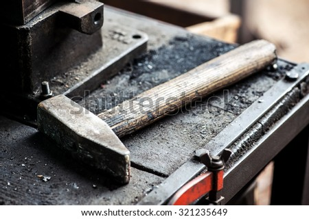 Heavy iron mallet or hammer lying on a grungy workbench in a factory or workshop conceptual of industrial repair, maintenance or manufacturing