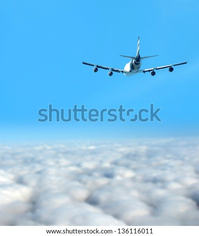Heavy jumbo jet airplane flying above the clouds - stock photo