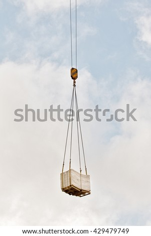 heavy load of bricks hanging on the hook of a crane, blue cloudy sky background