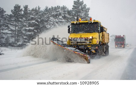 Heavy machinery cleaning road after snowstorm