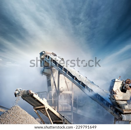 Heavy machinery of gravel production in quarry. Stones breaking factory with pit and moving conveyor belt loading crushed stones - stock photo