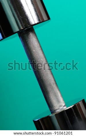 Heavy Metal Dumbbell on Turquoise Background - stock photo