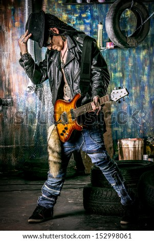 Heavy metal musician is playing electrical guitar in the old garage. - stock photo
