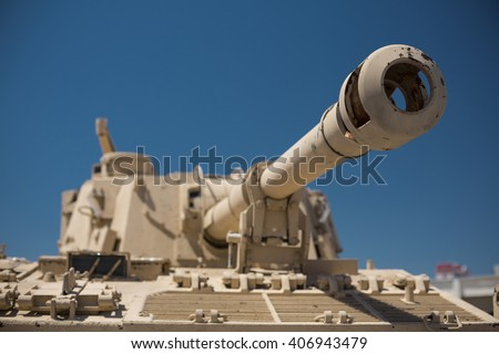 Heavy military desert camouflage tank turret gun aiming and ready to fire - stock photo