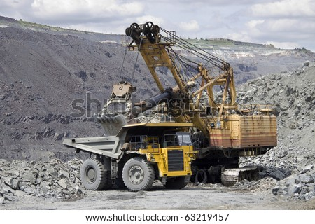 Heavy mining dump truck being loaded with iron ore - stock photo