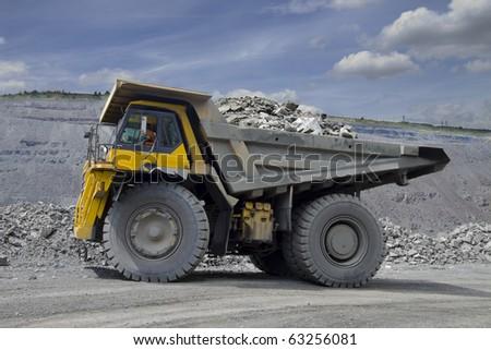 Heavy mining dump truck driving along the opencast - stock photo