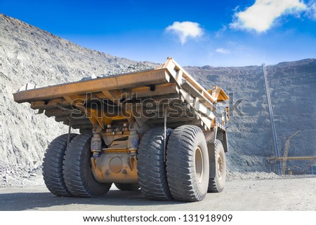 Heavy mining dump truck driving along the opencast. Ore conveyor at background