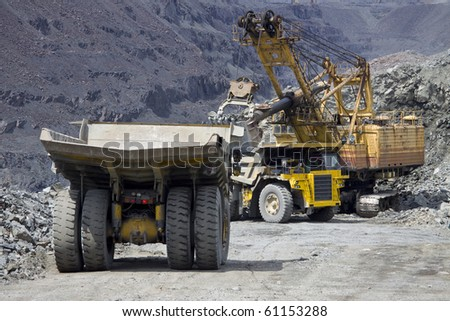 Heavy mining dump trucks waiting in line for being loaded with iron ore