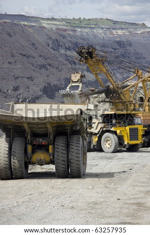 Heavy mining dump trucks waiting in line for being loaded with iron ore - stock photo