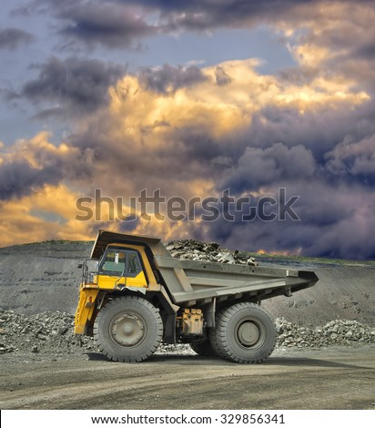 Heavy mining truck loaded with iron ore on the opencast with stormy clouds